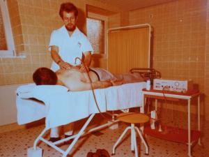 Pfleger mit Patient auf Liege, hier eine Art Massage mit einer Saugglocke, evtl. Hitze- und Kältetherapie o.ä. 1977.